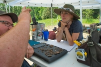 Dr. Andy Speer (L) examines artifacts extracted from pit by Miranda (R).